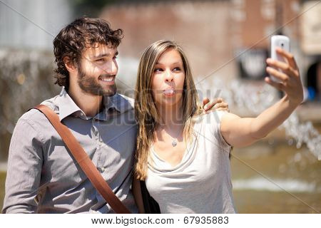 Couple of turists taking a selfie in the city