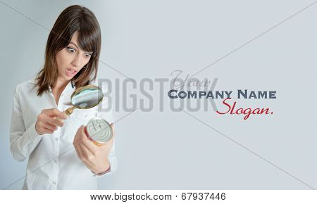 Shocked young   woman inspecting a can�?�¢??s nutrition label with a magnifying glass