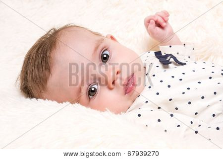Beautiful Baby Girl In Spotty Top On Cream Fur Rug