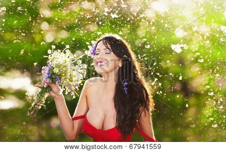 Young voluptuous brunette holding  a wild flowers bouquet in a sunny day.Portrait of beautiful woman