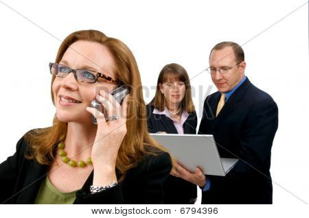 Business Woman On Phone With Coworkers Behind