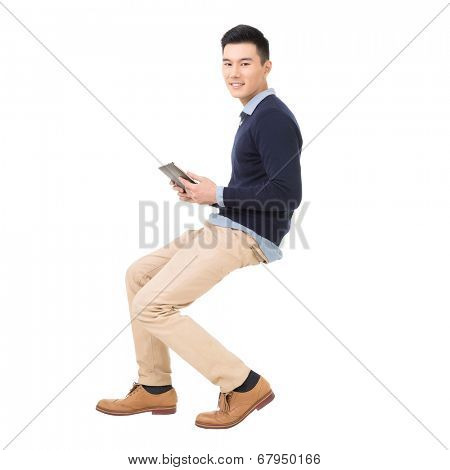 Handsome Asian guy sit and use pad, full length portrait isolated on white background.