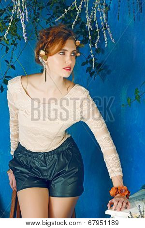 portrait of a beautiful woman with red hair in braided hairstyle. wearing leather shorts and lace top on grunge painted background