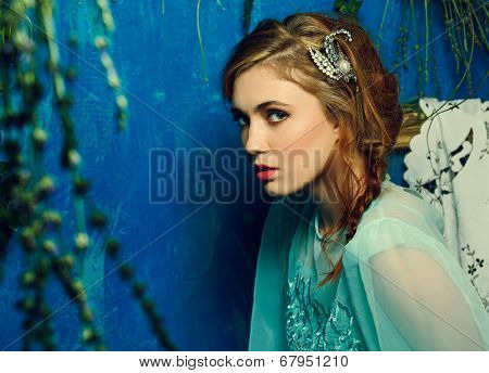 Portrait of a young woman with braid hairstyle on blue grunge texture background