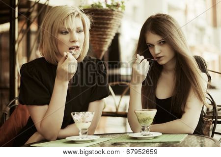 Two young women eating an ice cream at sidewalk cafe