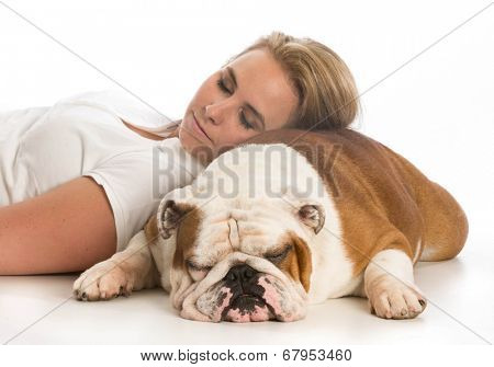 woman laying down with head resting on english bulldog