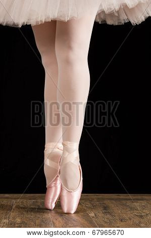 A ballet dancer standing on toes on wood floor