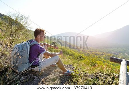 Hiker With Backpack Relaxing On A Path Of Mountain