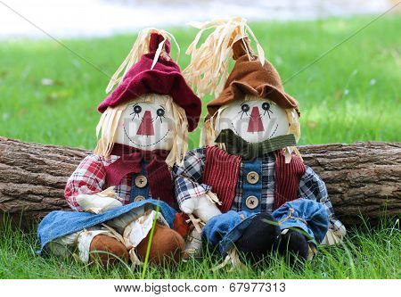 Boy and girl scarecrows sitting on grass by log next to lake