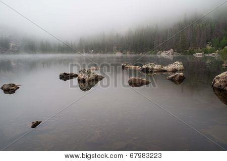 Rocks Reflected In A Foggy Lake