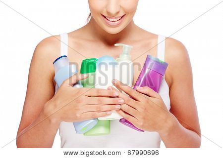 Close-up of young woman holding containers with shower gel, lotion and liquid soap