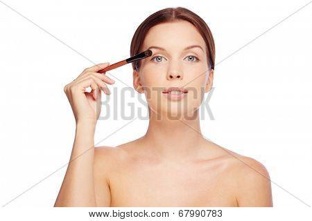 Fresh girl applying eyeshadows with brush over white background