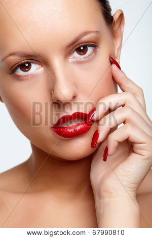 Gorgeous woman with red lips and fingernails looking at camera