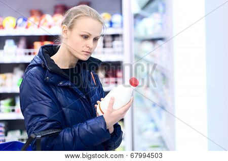 Woman in grocery holding milk