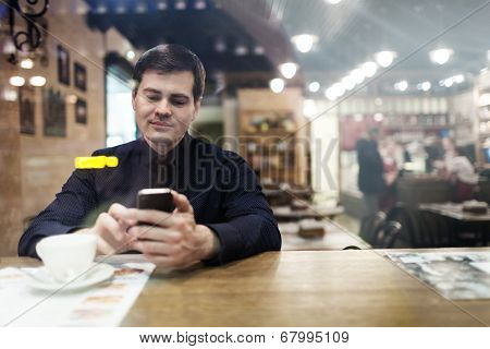 Gentleman sitting at the table using phone