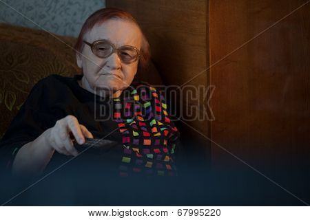 Old woman at home watching TV and changing channels