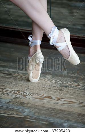 Dancing feet in ballet shoes on wooden floor