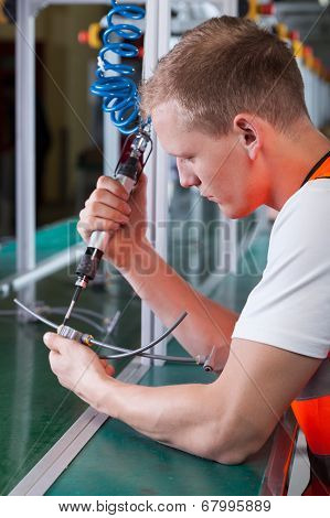 Factory Worker With Pneumatic Screwdriver