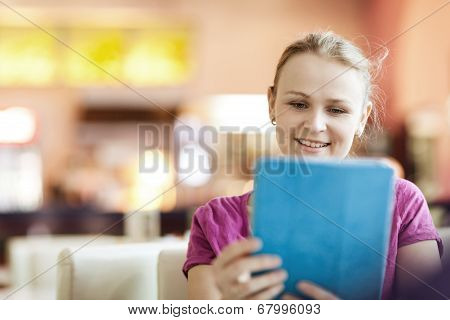 Young happy woman in cafe with tablet PC