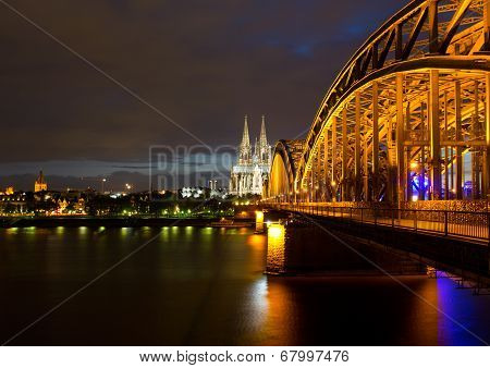 Bridge On River Rhine Against Cologne Cathedral At Night