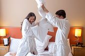 stock photo of pillow-fight  - Happy Couple Having Pillow Fight in Hotel Room - JPG