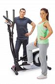 stock photo of elliptical  - Young man and woman with elliptical cross trainer - JPG