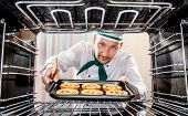 foto of pastry chef  - Chef prepares pastries in the oven - JPG