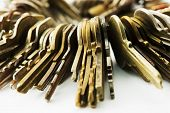 foto of bundle  - Many brass and chrome old keys on white table - JPG
