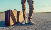 stock photo of old suitcase  - Traveler stands near the vintage suitcase on road face is not visible - JPG