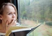 pic of passenger train  - Young woman on a train writing notes in a diary or journal staring thoughtfully out of the window with her pen to her lips as she thinks of what to write - JPG