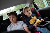 Постер, плакат: Children sitting in the car and looking at the road