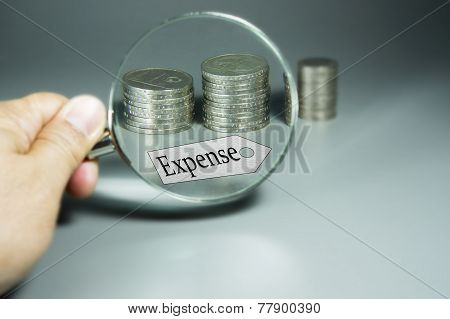 Magnifier, Expense Tag, And Stack Of Coins In The Backdround