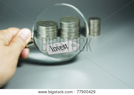 Magnifier, Invest Tag, And Stack Of Coins In The Backdround