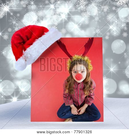 Festive little girl wearing red nose against shimmering light design on grey