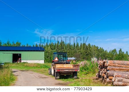 Old Rusty Tractor With Firewood In The Barn