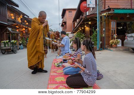 People Put Food Offerings In A Buddhist Monk's Alms Bowl For Good Merit