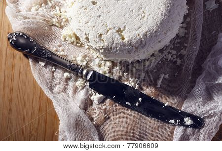 Cottage cheese and metal knife on gauze on cutting board closeup