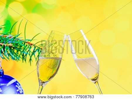 Champagne Flutes With Golden Bubbles On Christmas Decoration Yellow Bokeh Background