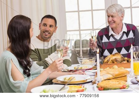 Smiling family toasting during christmas dinner at home in the living room