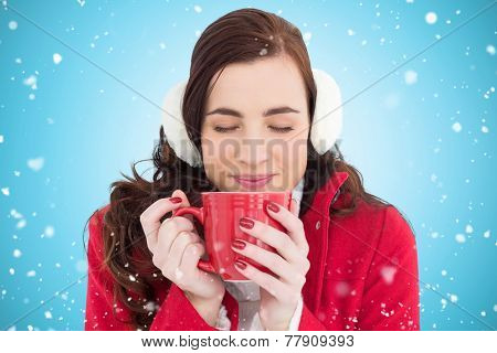 Woman in winter clothes enjoying a hot drink eyes closed against blue vignette