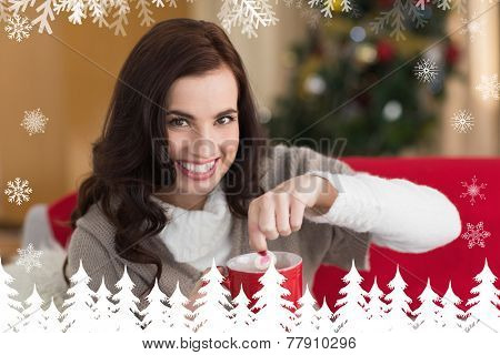 Brunette dunking marshmallow in hot chocolate at christmas against fir tree forest and snowflakes