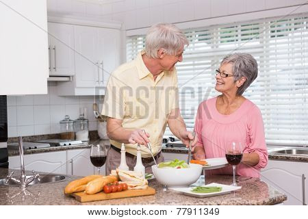 Senior couple preparing lunch together at home in the kitchen