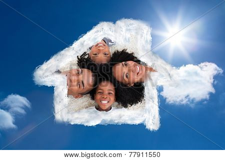 Family on floor with heads together against bright blue sky with clouds