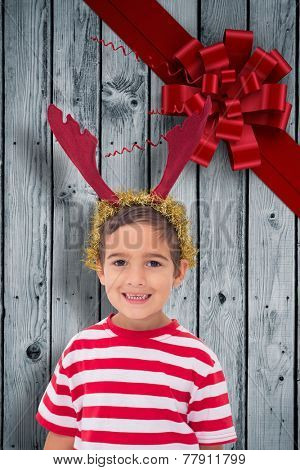 Cute little boy wearing antlers against wood with festive bow