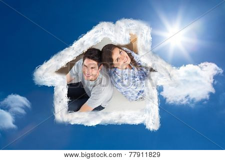 Overview of a happy couple sitting back-to-back against bright blue sky with clouds