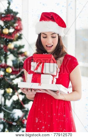 Surprised brunette in red dress holding pile of gift against snow falling