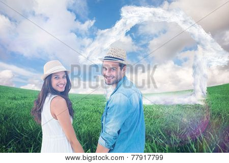 Happy hipster couple holding hands and smiling at camera against green field under blue sky