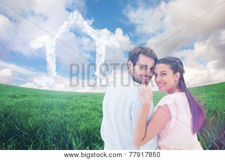 Attractive young couple smiling at camera against green field under blue sky