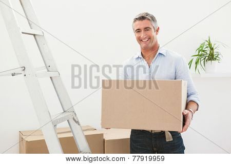 Smiling man holding cardboard box next a stepladder at apartment