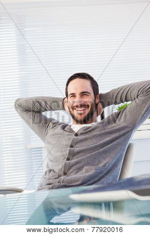 Relaxed casual businessman leaning back at his desk in the office